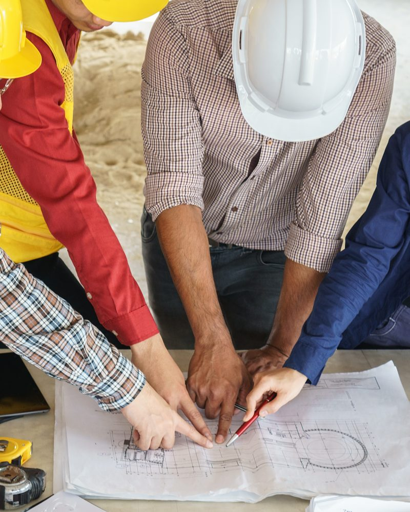 business people group on meeting and presentation with construction engineer architect looking building model and blueprint plans